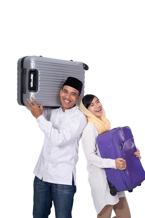 Pares asi?ticos musulmanes con la maleta del viaje imagen de archivo
