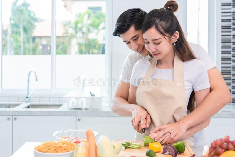 Pares asi?ticos que cocinan y que cortan la verdura en cocina junto Mujer de enseñanza del hombre a preparar la comida en hogar G fotos de archivo