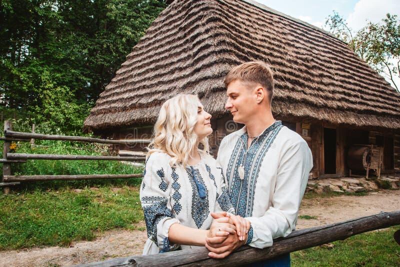 Pares asombrosos de la boda que llevan a cabo las manos y que abrazan contra un fondo de una casa de madera foto de archivo libre de regalías
