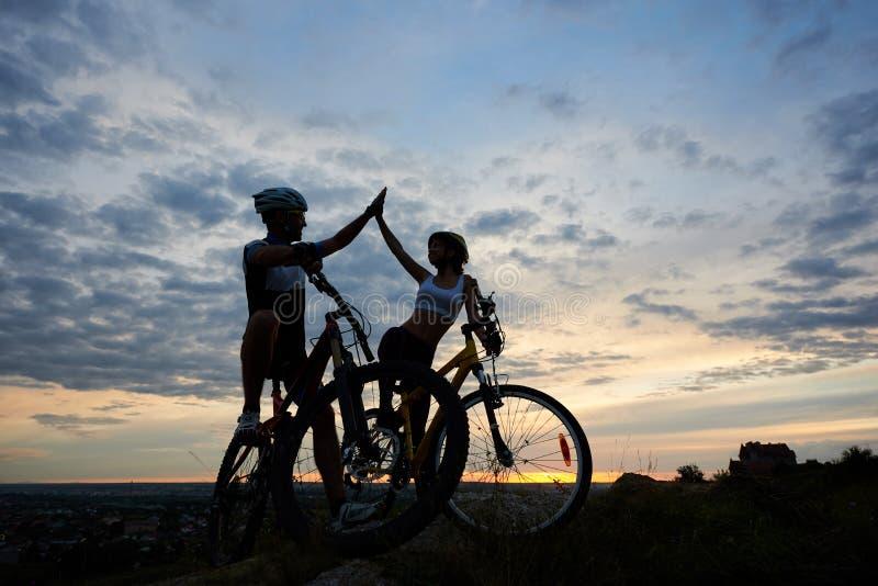 Pares ativos nas bicicletas que highing cinco e vista de se imagens de stock royalty free