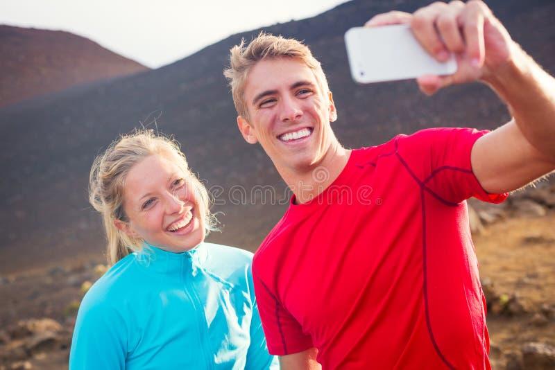 Pares atléticos atractivos jovenes que toman la foto de ellos mismos con fotografía de archivo libre de regalías
