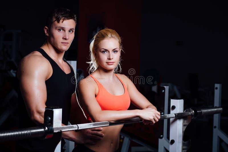 Pares atléticos - el hombre y la mujer descansan entre los ejercicios cerca del barbell en gimnasio foto de archivo