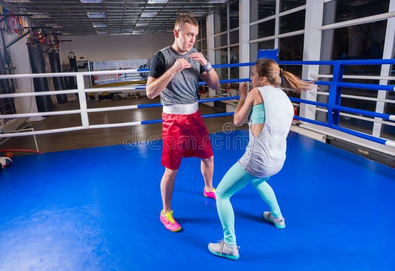 Pares atléticos en el encajonamiento practicante de la ropa de deportes en boxin regular imágenes de archivo libres de regalías