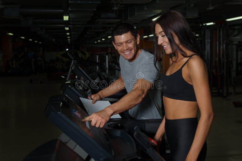 Pares atléticos no treinamento no clube de aptidão imagens de stock