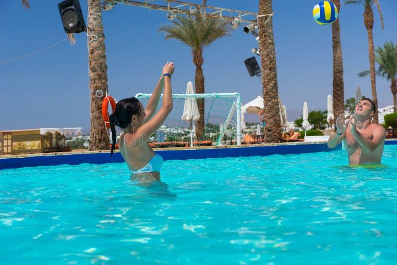 Pares atléticos novos que jogam o voleibol na piscina fotografia de stock royalty free
