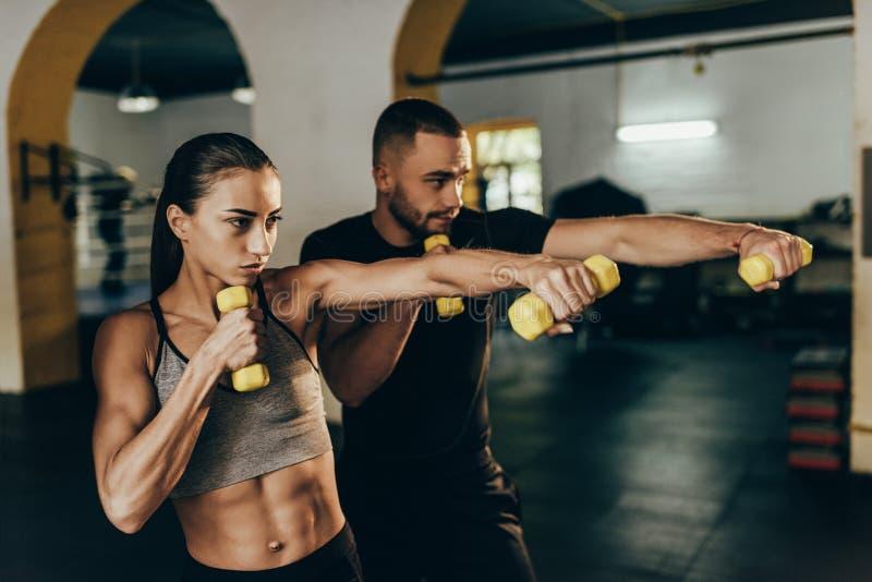 Pares atléticos que ejercitan con pesas de gimnasia imagen de archivo libre de regalías