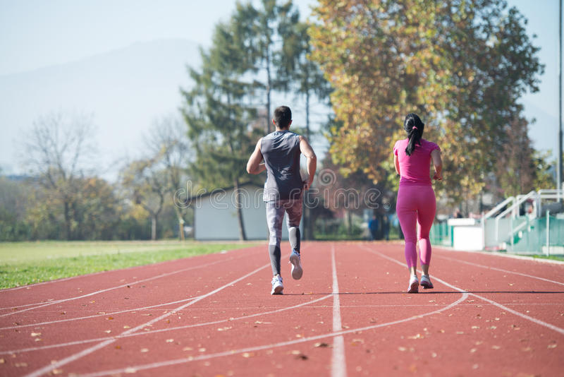 Pares atléticos que esprintan en la pista corriente foto de archivo