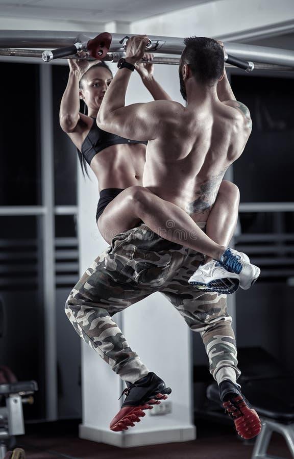 Pares atléticos que fazem tração-UPS junto imagens de stock royalty free