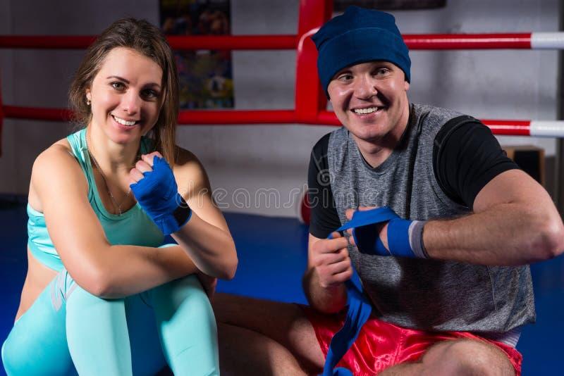Pares atléticos sonrientes del boxeo que preparan los vendajes fotografía de archivo
