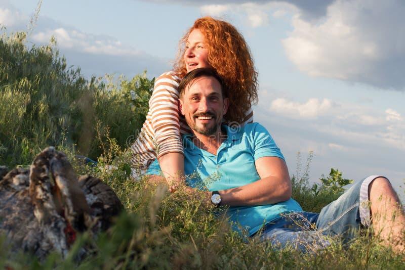 Pares atractivos cariñosos felices que ponen por la hoguera que abraza en hierba y nubes El par ama comida campestre fuera de la  fotografía de archivo