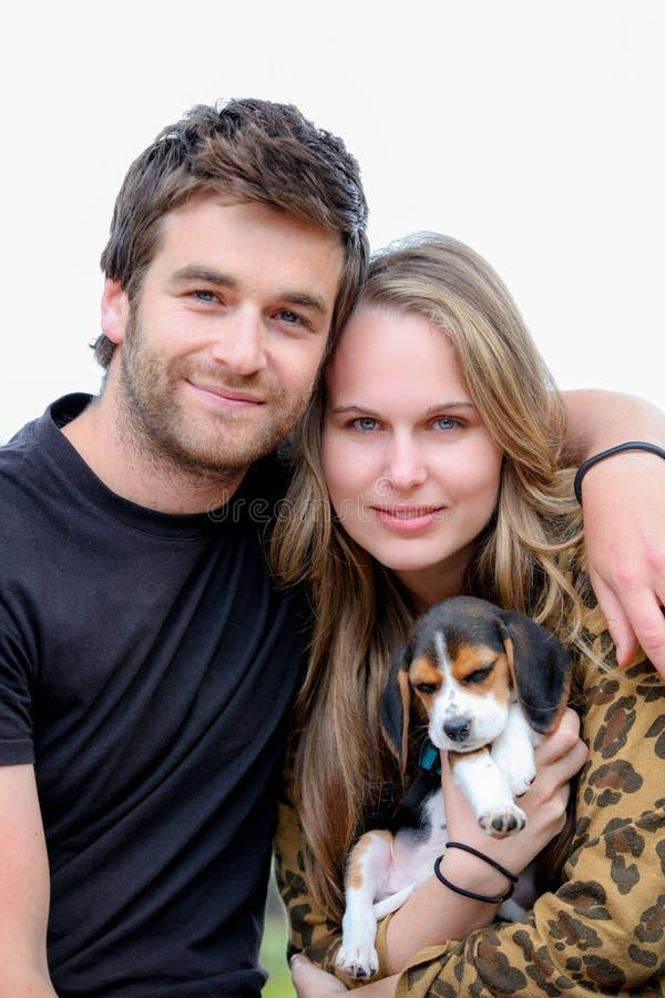 Pares atractivos con el perro casero de la familia foto de archivo
