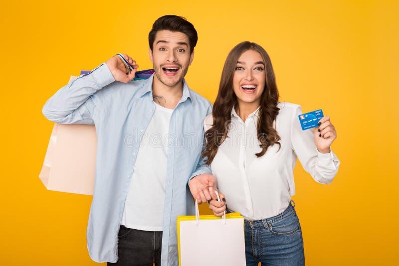 Pares atractivos con los bolsos de compras y la tarjeta de crédito imágenes de archivo libres de regalías