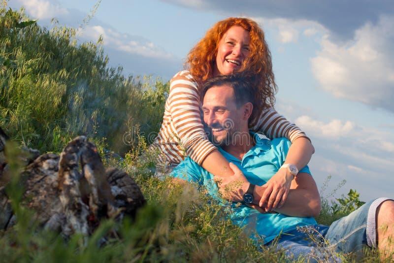 Pares atractivos de la sonrisa cariñosa feliz que ponen por la hoguera que abraza en hierba y nubes El par ama los relojes casual imagenes de archivo