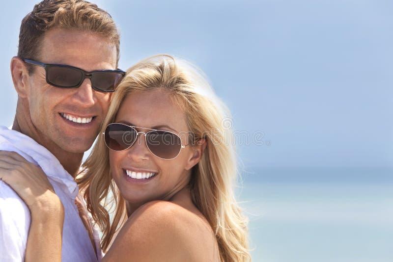 Pares atractivos del hombre y de la mujer felices en la playa imagen de archivo