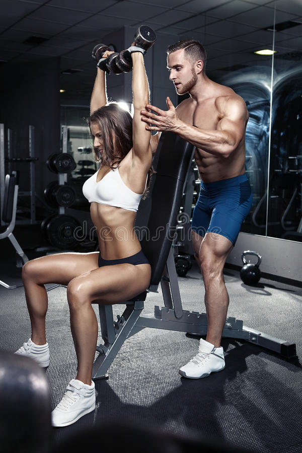 Pares atractivos deportivos jovenes hermosos en gimnasio fotografía de archivo