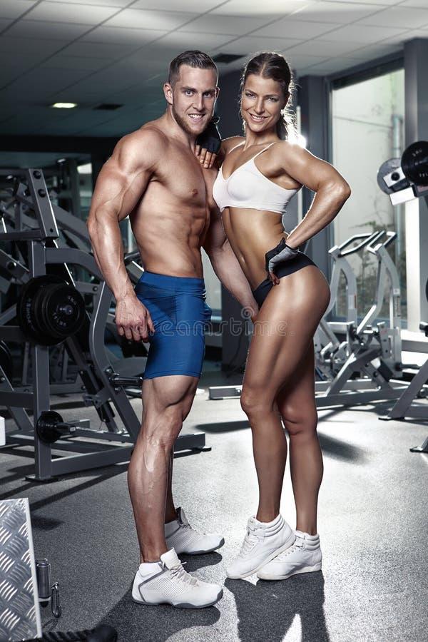 Pares atractivos deportivos jovenes hermosos en gimnasio foto de archivo libre de regalías