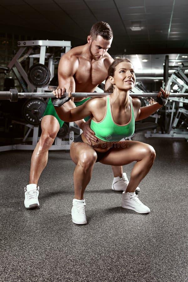 Pares atractivos deportivos jovenes hermosos en gimnasio imagen de archivo