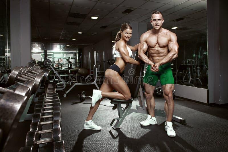 Pares atractivos deportivos jovenes hermosos en gimnasio fotos de archivo libres de regalías
