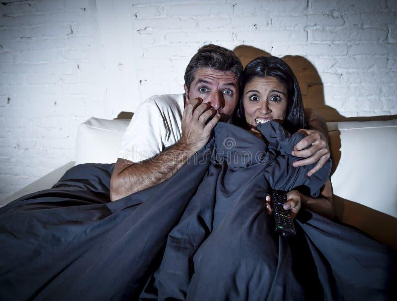 Pares atractivos en casa que gozan mirando la cubierta de la película de terror de la televisión con la manta imagenes de archivo