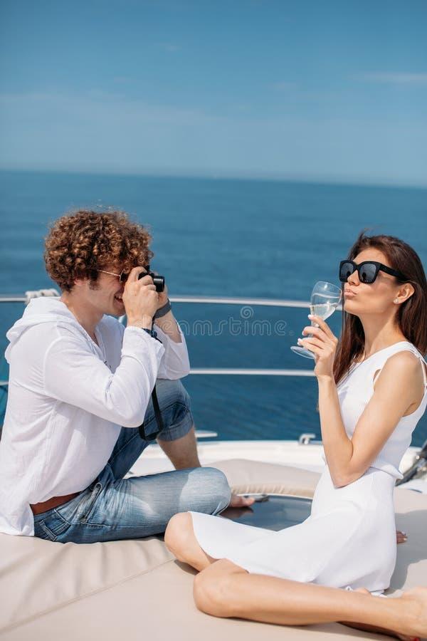 Pares atractivos en el yate El hombre joven está tomando la foto de su novia imagen de archivo libre de regalías