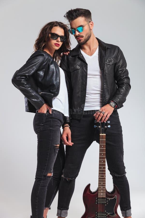 Pares atractivos en las chaquetas de cuero que sostienen la guitarra eléctrica foto de archivo libre de regalías