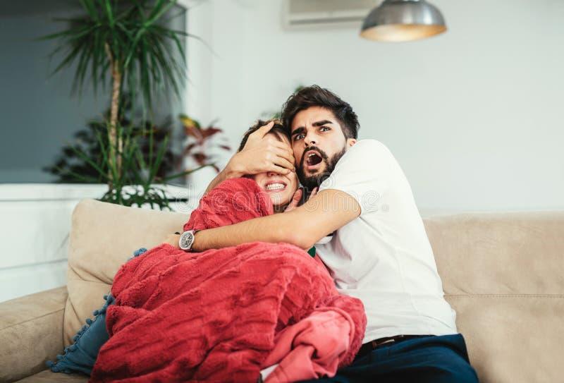 Pares atractivos felices jovenes que se divierten en casa que goza viendo la TV fotografía de archivo