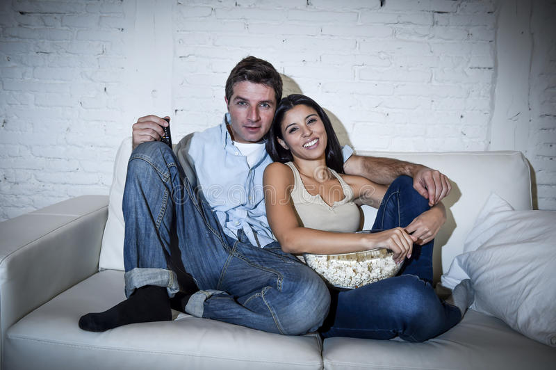 Pares atractivos felices que se divierten en casa que goza mirando la televisión relajada imágenes de archivo libres de regalías