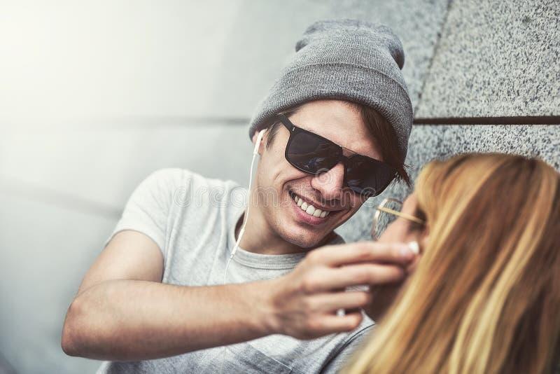 Pares atractivos jovenes que escuchan la música en los mismos pares de auriculares, vestidos en ropa elegante contra un fondo de  fotografía de archivo libre de regalías