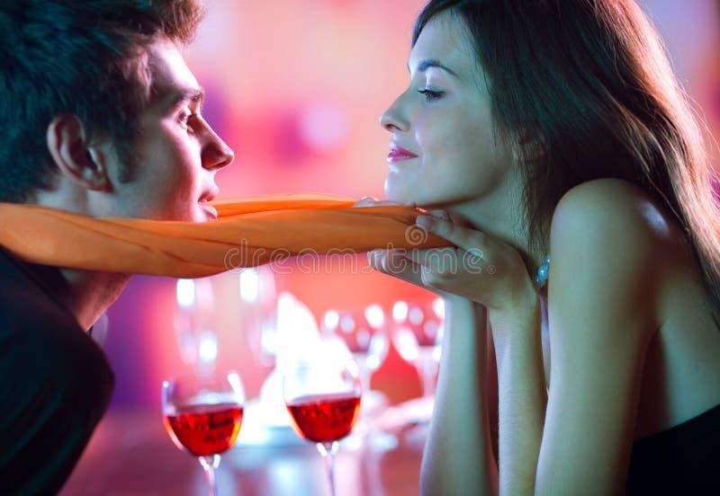 Pares atractivos jovenes que se besan en el restaurante, celebrando foto de archivo libre de regalías