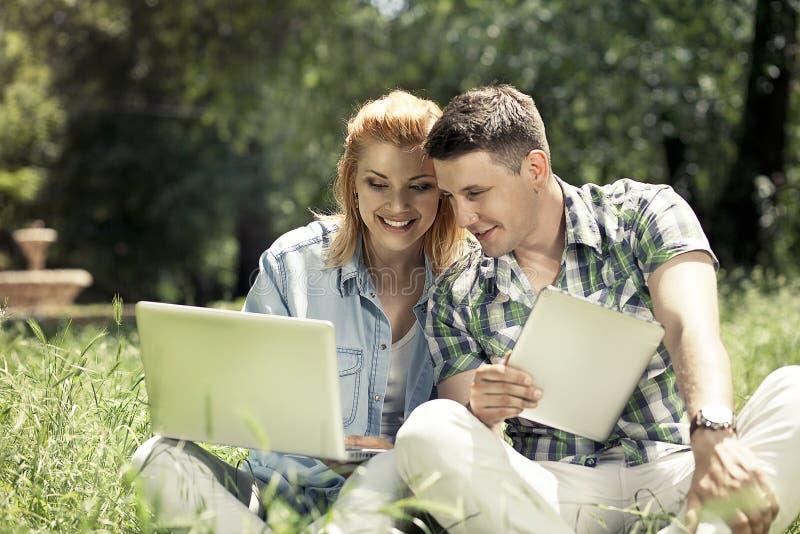 Pares atractivos jovenes que se sientan en la hierba, mirando el ordenador portátil fotografía de archivo