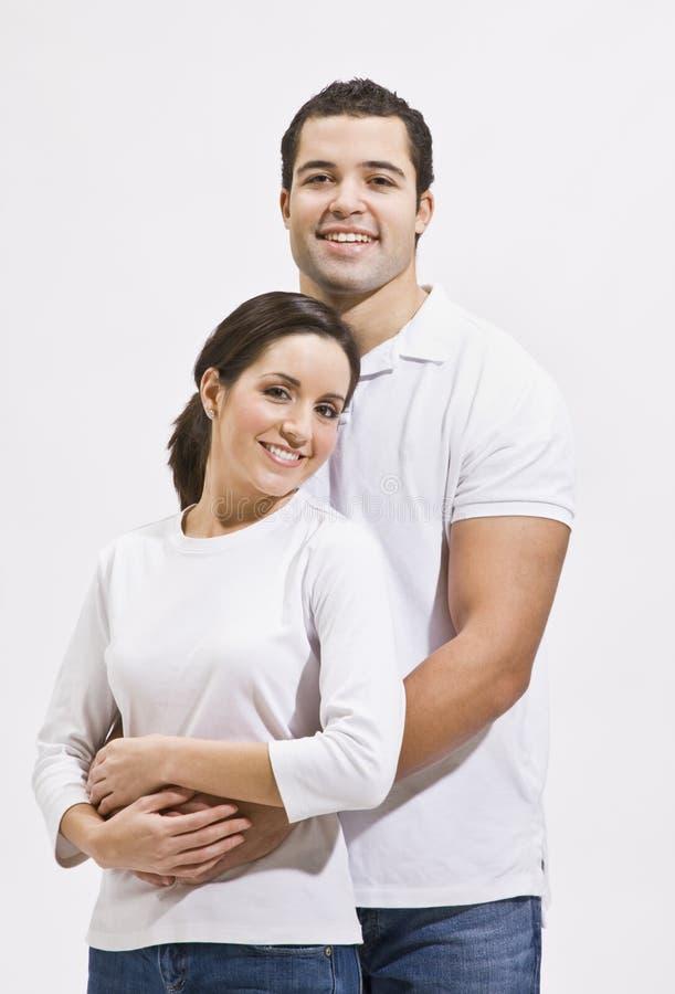 Pares atractivos que abrazan y que sonríen foto de archivo libre de regalías