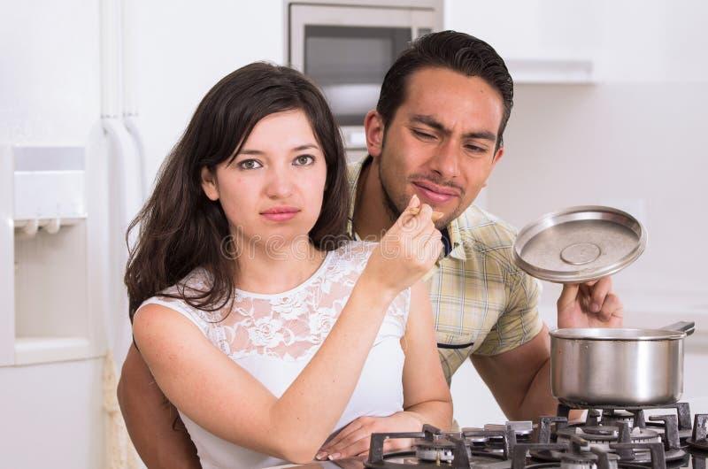 Pares atractivos que cocinan junto la comida desagradable fotos de archivo