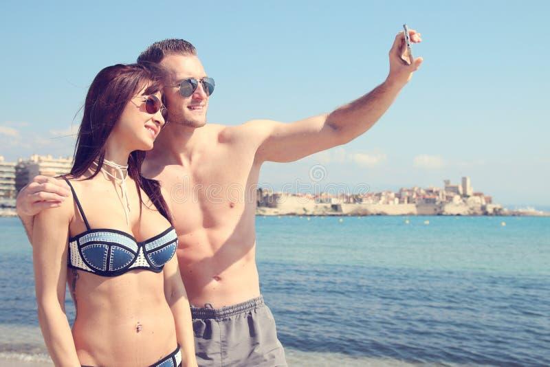 Pares atractivos que hacen un selfie delante de la playa imagen de archivo libre de regalías