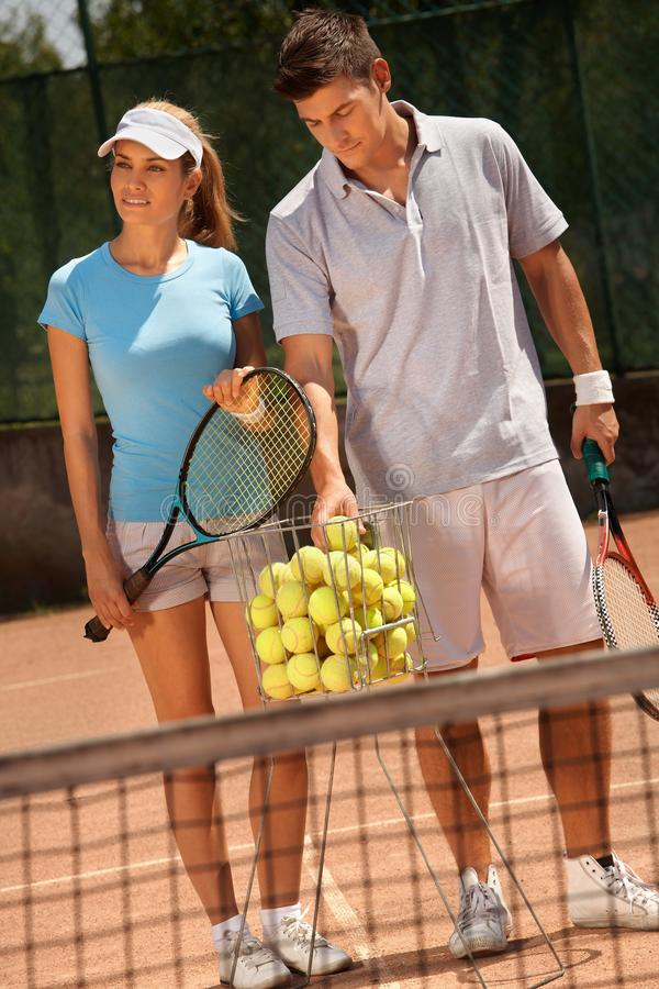 Pares atractivos que juegan a tenis fotografía de archivo