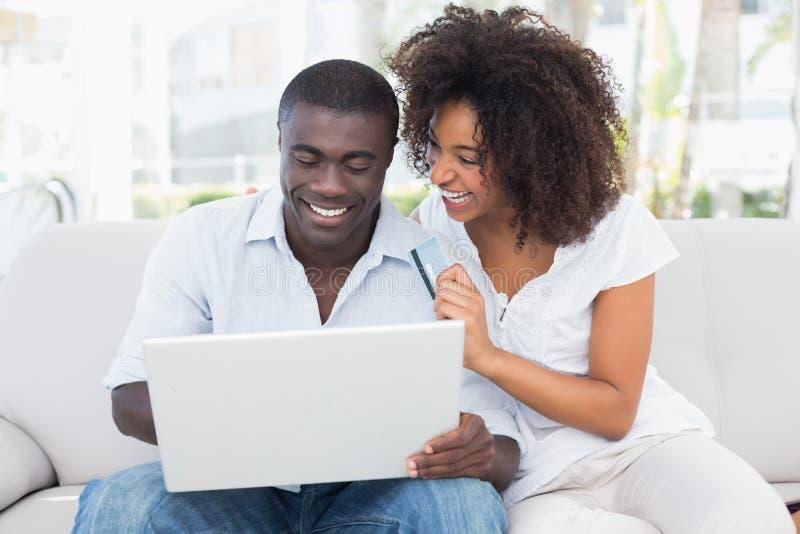 Pares atractivos usando el ordenador portátil junto en el sofá a hacer compras en línea imágenes de archivo libres de regalías