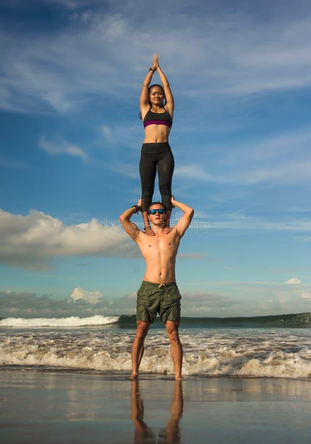 Pares atractivos y concentrados jovenes de los acr?batas que practican la balanza de la yoga del acro y el ejercicio de la medita fotografía de archivo libre de regalías