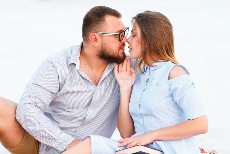 Pares atrativos bonitos que sentam-se junto na praia branca da areia, olhando-se, pares novos beijando na praia, amor, ro fotos de stock