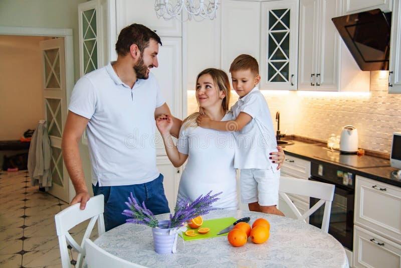 Pares atrativos com a mulher gravida que come o café da manhã na cozinha junto com a criança foto de stock royalty free