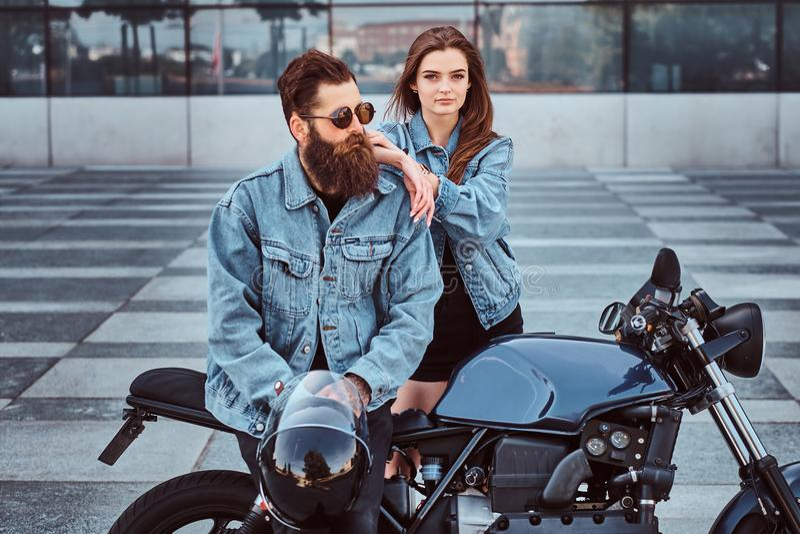 Pares atrativos do moderno - homem brutal farpado nos óculos de sol e no revestimento das calças de brim que senta-se em uma moto imagem de stock