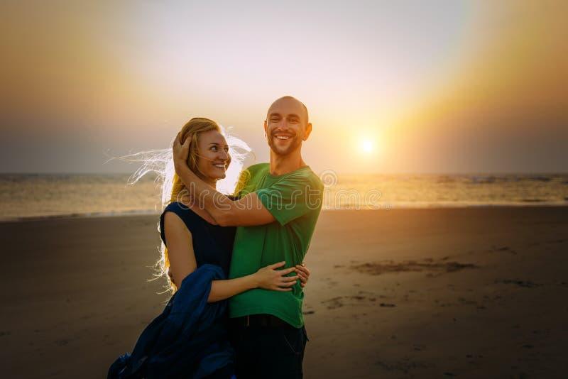 Pares atrativos em abraços e em risos do amor na praia no por do sol Os povos felizes descansam no mar Luminoso brilhante do sol fotos de stock