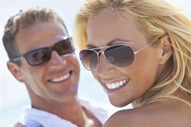 Pares atrativos felizes da mulher e do homem na praia fotos de stock