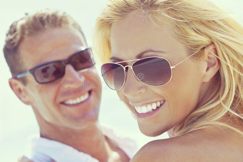 Pares atrativos felizes da mulher e do homem nos óculos de sol na praia imagem de stock