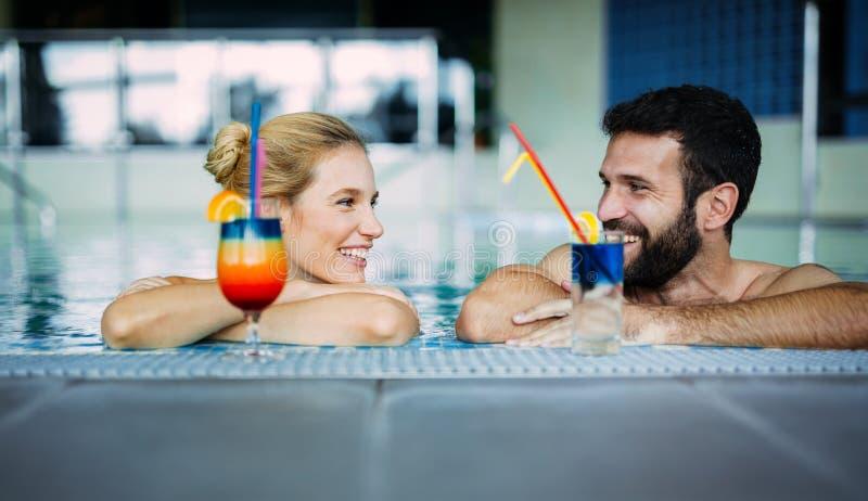 Pares atrativos felizes que relaxam na piscina fotos de stock