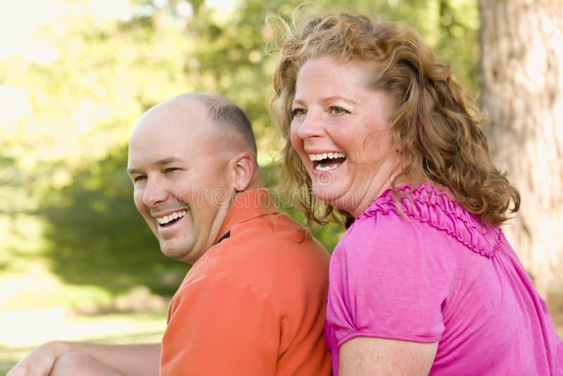 Pares atrativos felizes que riem no parque imagem de stock royalty free