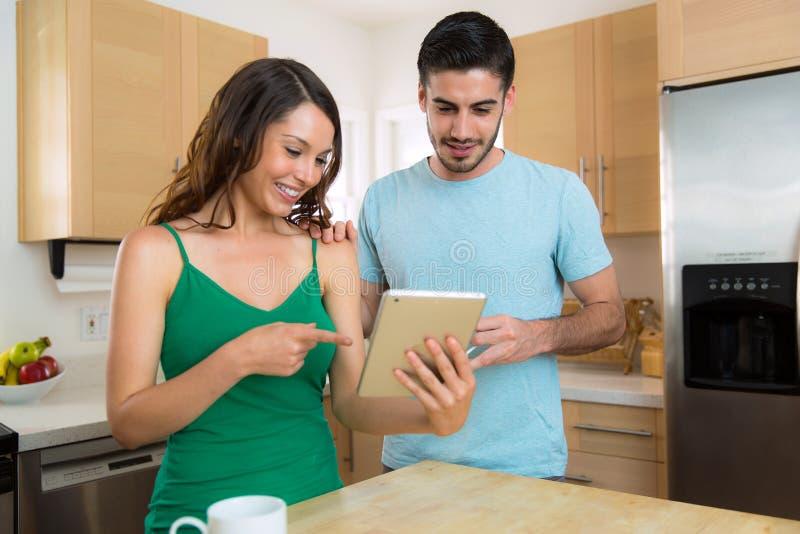 Pares atrativos novos felizes em casa que olham uma tabuleta esperta que consulta o Internet imagem de stock royalty free