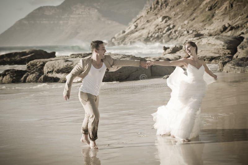 Pares atrativos novos que flertam ao longo do branco vestindo da praia fotografia de stock royalty free