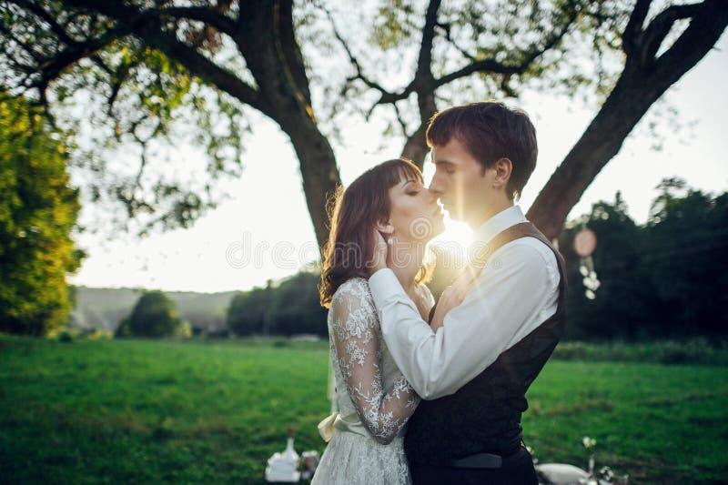 Pares atrativos que apreciam o piquenique romântico do por do sol no país fotografia de stock