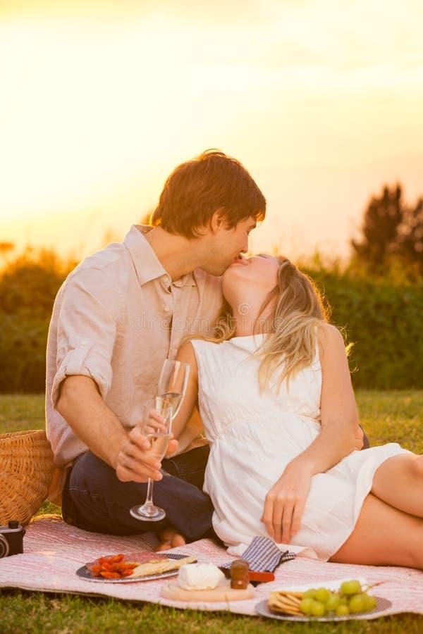 Pares atrativos que beijam no piquenique romântico imagem de stock