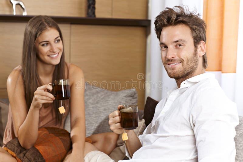 Pares atrativos que comem o chá em casa fotografia de stock royalty free