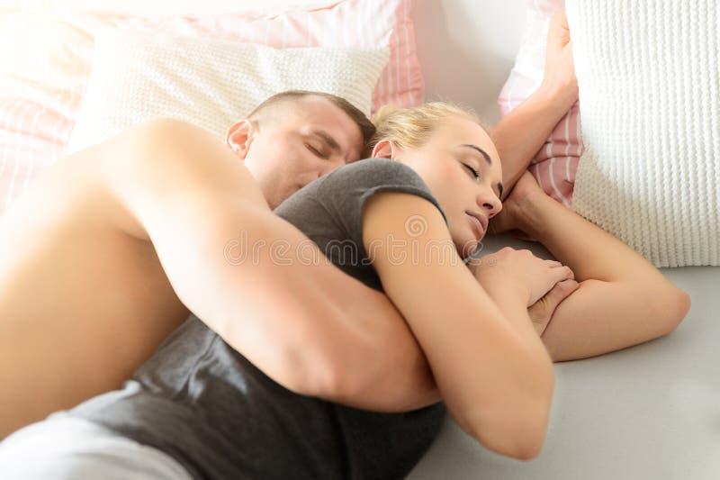 Pares atrativos que dormem junto na cama que afaga Conceito do amor e do relacionamento foto de stock